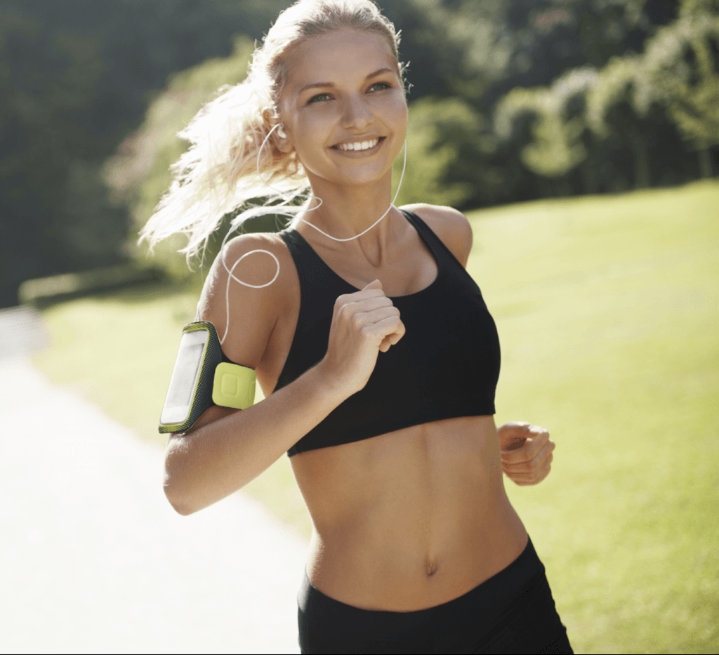 Woman smiling and running with music player strapped to arm
