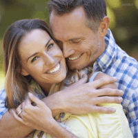 Man and woman hugging and smiling outdoors