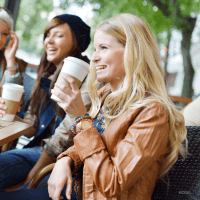 Women laughing together while drinking coffee