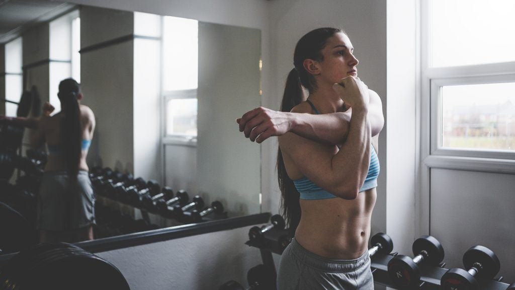 Woman stretching after a workout in the gym