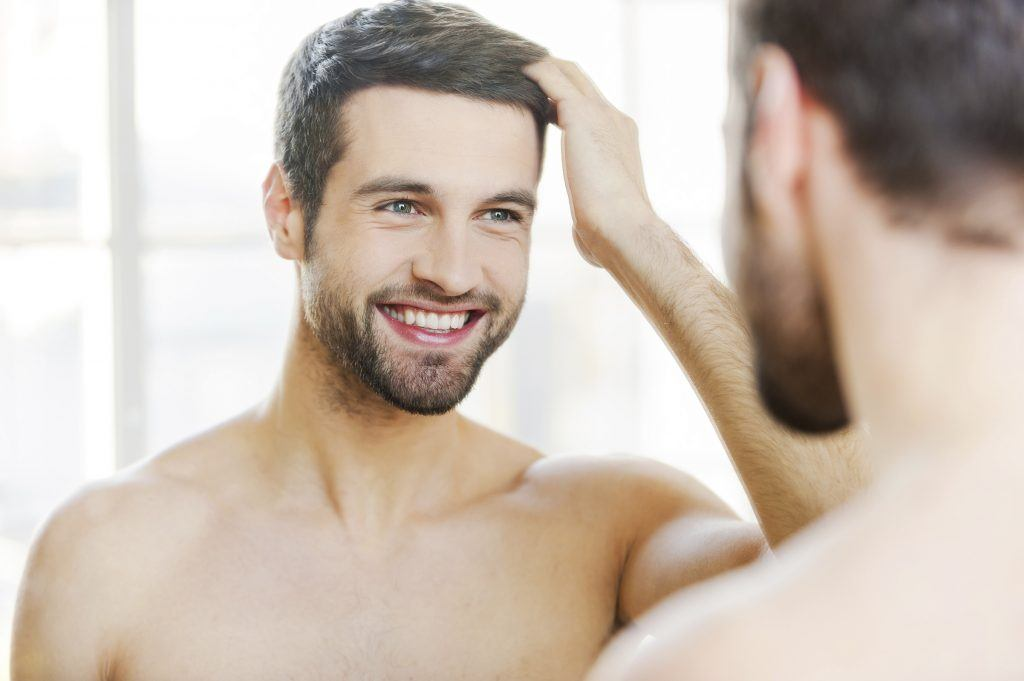 Man smiling and touching hair in the mirror