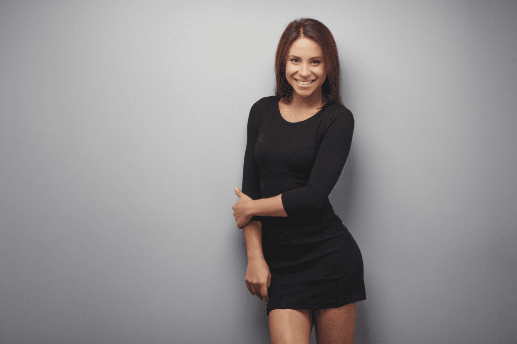 Woman in black dress smiling near a wall