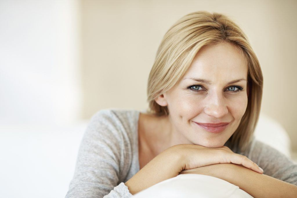 Woman smiling while sitting on couch