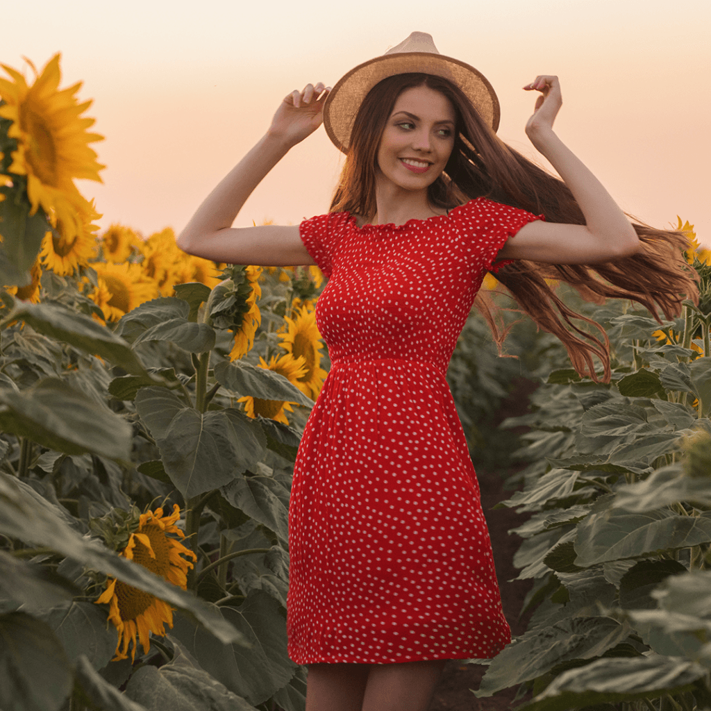 Woman in red dress and straw hat standing in sunflower field