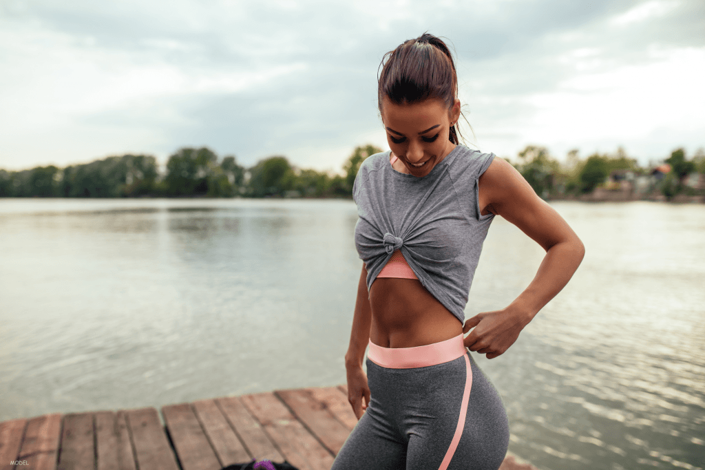 Woman in grey athletic clothes posing near a lake