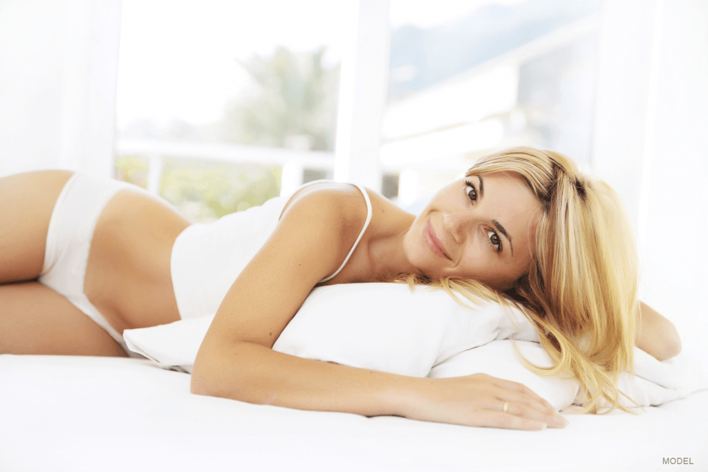 Woman in white loungewear resting on a bed