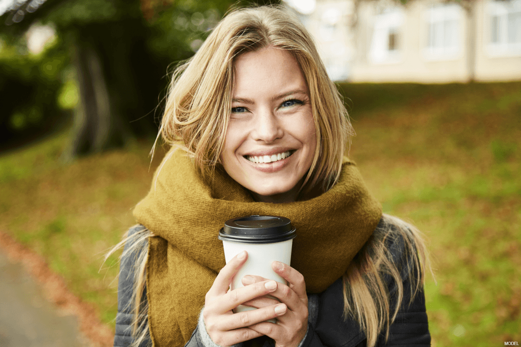 Woman smiling while wearing a large scarf and holding a coffee cup
