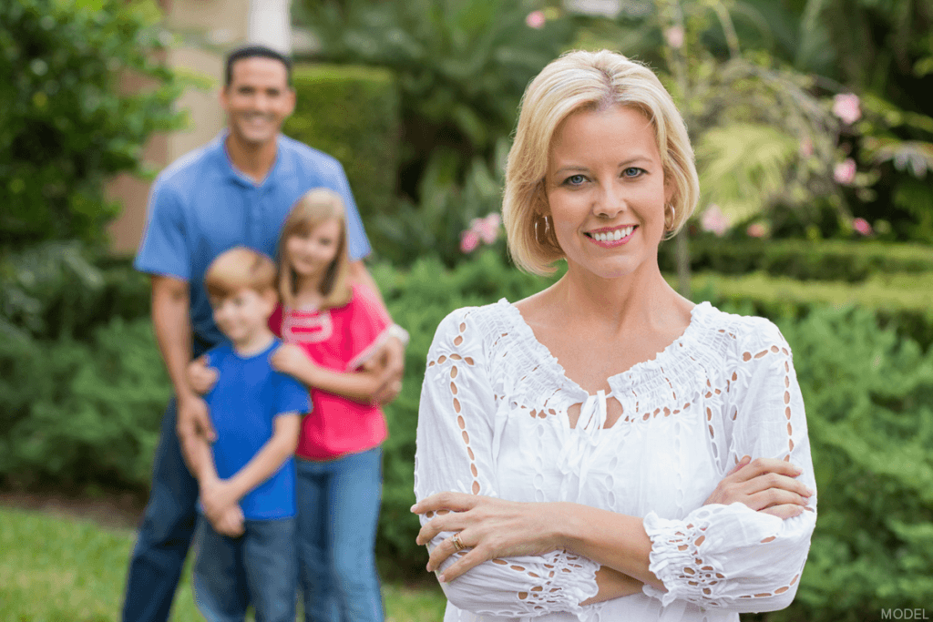 Woman smiling outdoors with man, boy child, and girl child smiling in the background