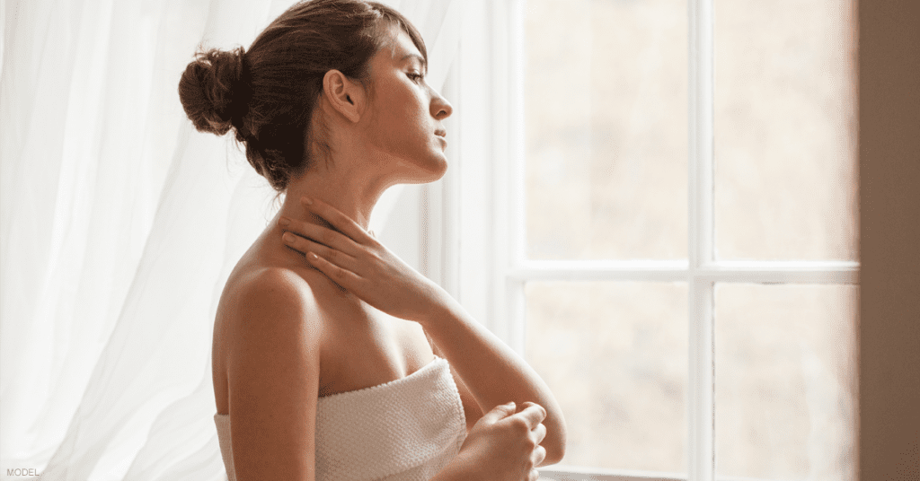 Woman feels her neck after a CoolSculpting for chin treatment.